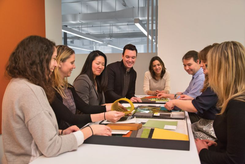 Looking head on, a group of 8 architects sit around the table analyzing fabrics and materials