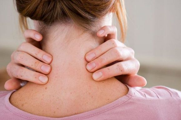 Woman holding back of neck showing neck strain