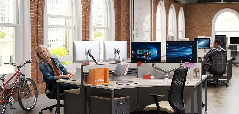 Two people sitting at desks with an open office plan - Nucleus task chair, Flagship mobile pedestal, Abound and Accelerate 120 degree corner worksurfaces, Concinnity O-Leg Support, Dual monitor arms