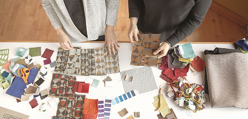 Bird's eye view of table top covered in colorful fabric swatches, scissors, and two people's hands touching fabrics