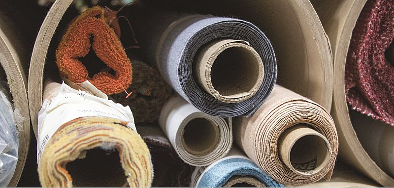 Variety of colorful, textured fabrics and materials rolled up and stacked