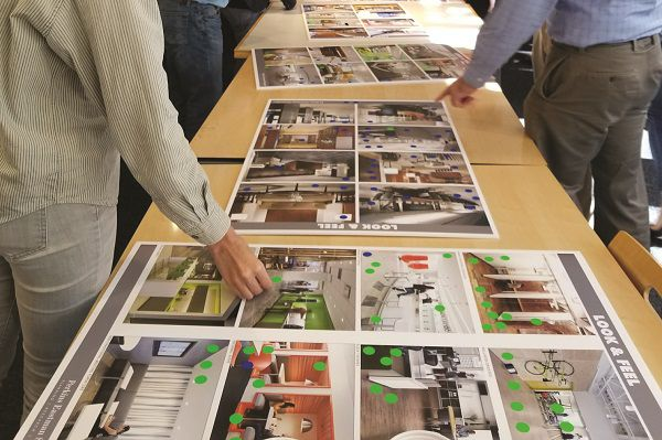 Three design concept posters laying on table tops with two different hands pointing at the images on the poster