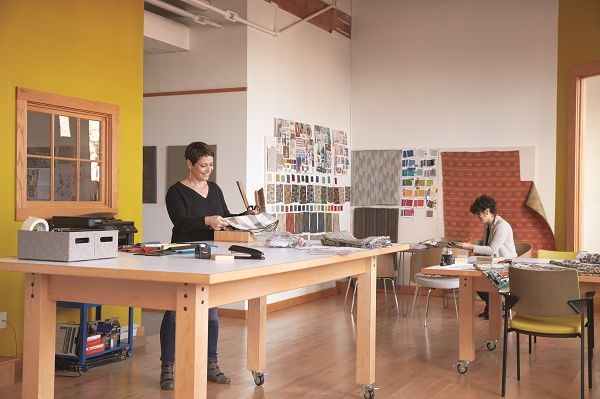 Room scene with Lori Roop in a design studio standing at a table looking at fabric with another designer working in the background